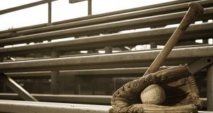 High school baseball practice with ball in glove and bat on bleachers.
