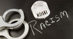 The word RACISM on a chalkboard with a police badge and handcuffs