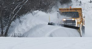 Snow Plow Truck on the road plowing through deep snow